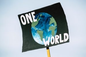 A protestor sign stating 'one world' with a globe at the centre