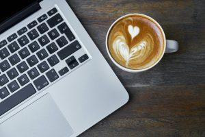 A coffee next to a laptop