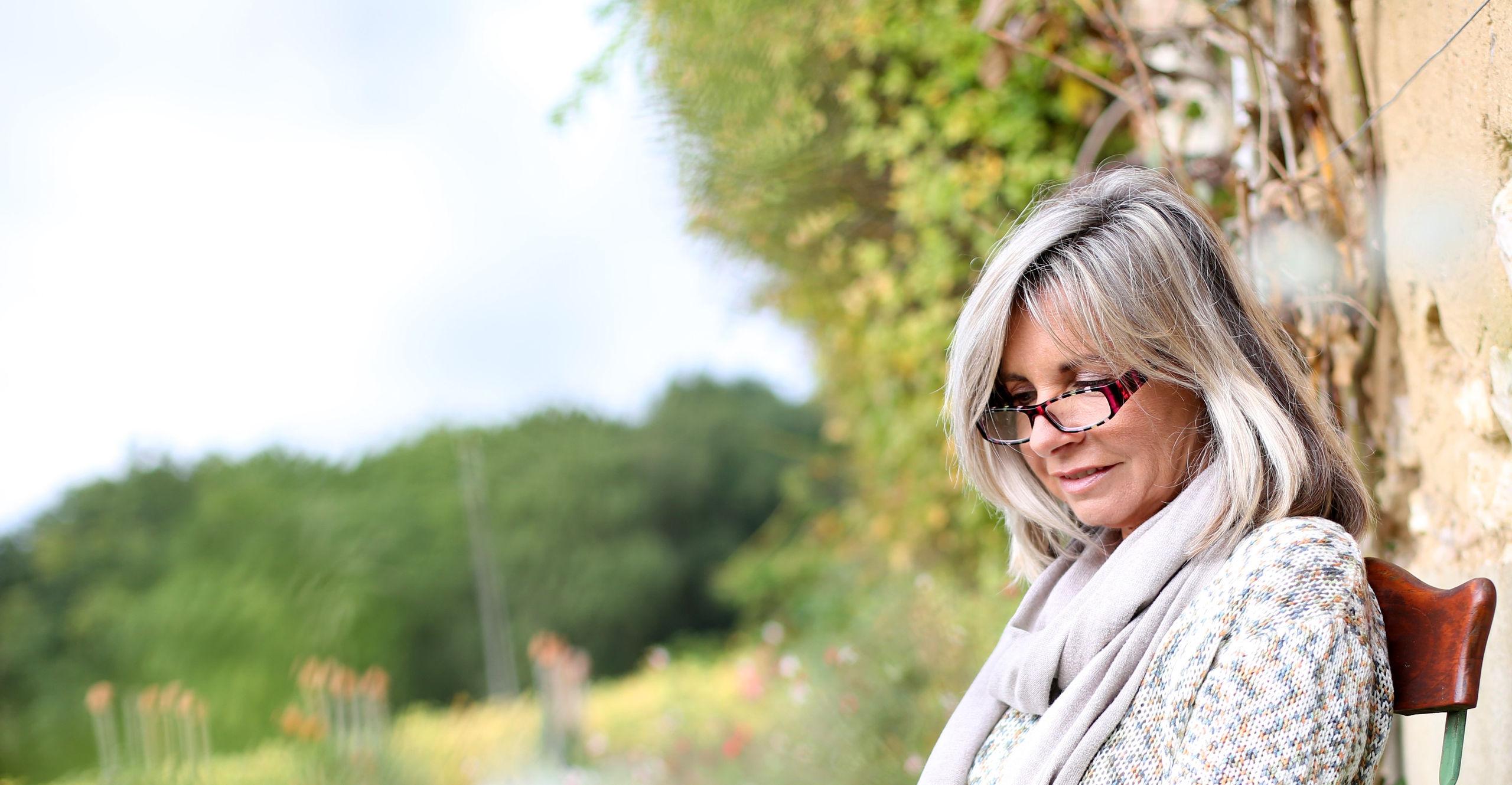 A lady sitting outside in a garden