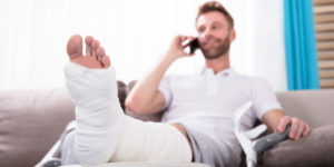 Man with a broken leg recovering on the sofa while talking on the phone